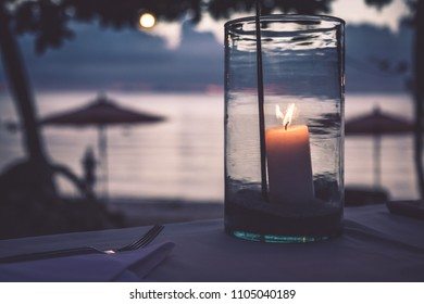 Romatic beach restaurant scene candles sunset blurred background