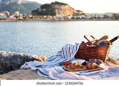 Romatic picnic on the beach in Denia, Spain. Picnic basket with red wine, bread, jam, cheese and jamon on a sunny day with sea and castle on background.