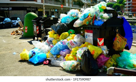 Rome, 22 July 2018: piles of garbage bags inside and outside a dumpster of the Roman municipal AMA, which hinders the circulation on the pavement in a district of Rome