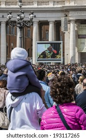 ROME - APRIL 13 2014: A group of believers, in St. Peter's Square on Palm Sunday during the Eucharistic blessing of Pope Francis. Pope Francis on the big screen. April 13, 2014, Vatican City, Italy