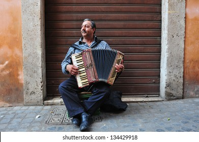 ROME - APRIL 29 2011:Gypsy man playing piano accordion at the Jewish ghetto  in Rome, Italy.The Roman Ghetto was established as a result of Papal bull promulgated by Pope Paul IV in 1555.