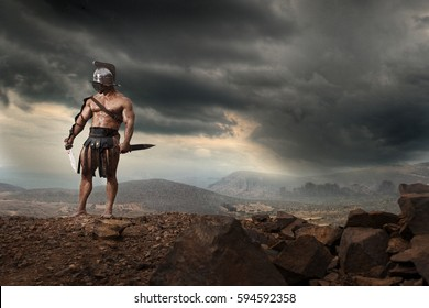 Rome gladiator attacking on dramatic outdoor nature. Ancient warrior with sword on blood sand