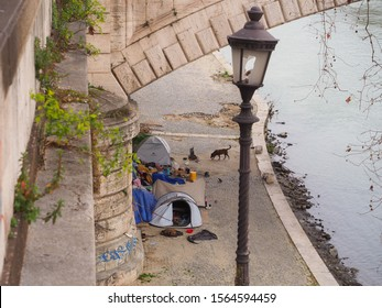 Rome / Italy - 03 07 2019: Homeless and beggar people live on the streets and under bridges. Tiber river embankment with camping tents, the home of impoverished and poor people, in city center of Rome