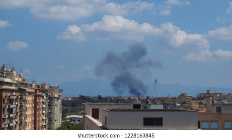 Rome / Italy - 08 13 2018: Capital of Italy. Rome. Fire in the city. Alarm. Black smoke above the houses. Misfortune. Catastrophe. Burns. Smoke billows. Dangerous. Polluted air