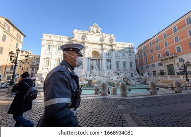 ROME, ITALY - 10 March 2020: A city Police man wearing a face mask walks across the deserted Trevi Fountain square. The  Government decreed a nationwide quarantine, with travel and gatherings ban.
