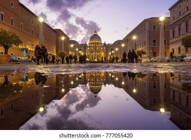 ROME, ITALY - 16 DECEMBER 2017 - The Saint Peter basilica in Vatican with the dome during the Christmas holidays. Here in particular the reflection in a puddle of Via della Conciliazione street