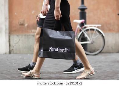 ROME, ITALY - 17 OCTOBER 2016: Pedestrian walks with her NeroGiardini shopping bag on Via del Corso, main shopping street in Rome, Italy