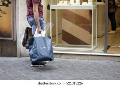 ROME, ITALY - 17 OCTOBER 2016: Pedestrian with his Zara shopping bag on Via del Corso, main shopping street in Rome, Italy