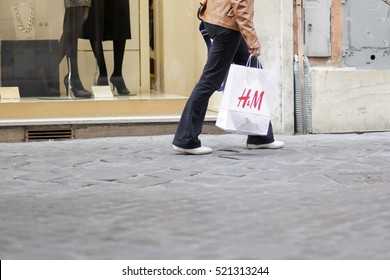ROME, ITALY - 17 OCTOBER 2016: Pedestrian walks with her H&M shopping bag on Via del Corso, main shopping street in Rome, Italy