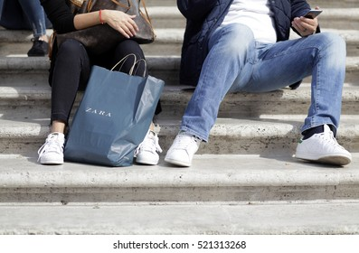 ROME, ITALY - 17 OCTOBER 2016: Pedestrians seated with his their Zara shopping bag on the Trinità dei Monti staircase, main shopping street in Rome, Italy