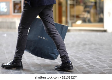 ROME, ITALY - 17 OCTOBER 2016: Pedestrian walks with his Zara shopping bag on Via del Corso, main shopping street in Rome, Italy