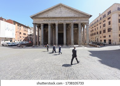 Rome, Italy - 19 May 2020: Men in business suits wearing face masks walk in group across the otherwise mostly empty Pantheon square in Rome, Italy.