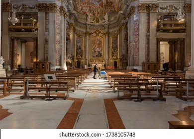 Rome, Italy - 19 May 2020: A worker polishes the marble floors between rows of benches in Saint Ignatius of Loyola church. Churches have reopened following coronavirus lockdown ease