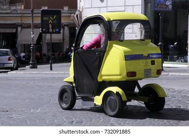 ROME, ITALY - 19 SEPTEMBER 2017: A mini electric car of Poste Italiane runs through the streets of Rome, Italy.