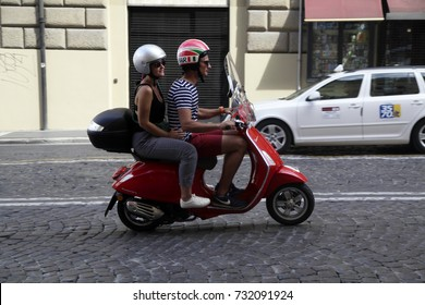 ROME, ITALY - 19 SEPTEMBER 2017: A young couple ride a Vespa scooter on the street in Rome, Italy. Vespa scooter is an italian symmbol.