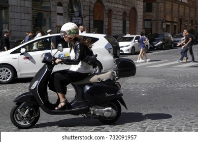 ROME, ITALY - 19 SEPTEMBER 2017: A young woman ride a Vespa scooter on the street in Rome, Italy. Vespa scooter is an italian symmbol.