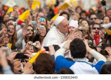Rome, Italy - April 04 2013: His Holiness Pope Francis I kisses a child during a prayer in front of St Peter' Basilica in Vatican City