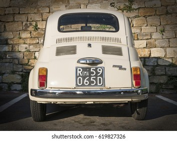 Rome / Italy - April 10, 2017: Vintage Fiat Nuova 500 parked in front of a stone wall in Rome, rear view. Built in 1957, this car was a cheap town car and a symbol of the economic boom.