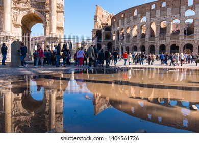 Rome, Italy - April 17, 2019: Tourists at the Arch of Constantine and the Colosseum in Rome, Italy.