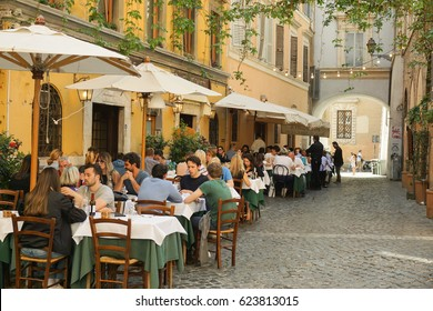 ROME, ITALY - APRIL 18, 2017: people are eating outdoors in a typical trattoria in Trastevere, historic district of Rome, Italy