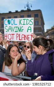 """ROME, ITALY - April 19, 2019: People taking part in Fridays For Future protest (School Strike For Climate, Greta Thunberg). Young woman and friends. Signs reading: """"Cool kids saving a hot planet"""""""