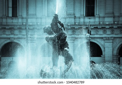 Rome, Italy - April 2012: The famous Fountain of the Naiads in the Piazza della Repubblica. Watery scene in cyan tones. Close up image of figure holding dolphin with building behind