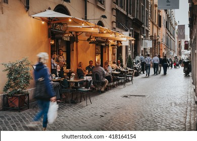 ROME, ITALY - APRIL 21 2016:Tourists in a charming restaurant terrace in the city center of Rome on April 21, 2016 in Rome, Italy. Rome has a lot of restaurants where people enjoy the italian dishes.