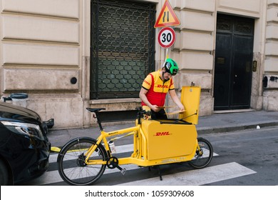 ROME, ITALY - April 4, 2017: On duty Italian DHL Postman with his delivery bicycle checking sender and recipient address on envelope to deliver parcel.