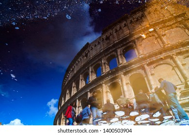 Rome, Italy - April 5, 2019: The Roman Colloseum or Flavian Amphitheather reflecting on rain water on the ground in Rome, Italy.