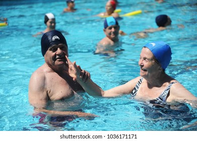 rome, italy - august 14th, 2017: a group of senior people having good time in a open swimming pool in rome