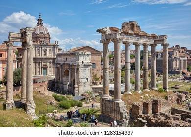 ROME, ITALY - AUGUST 15, 2018: Tourists in the Roman Forum at Temple of Saturn against Arch of Septimius Severus. Historical center of Rome is UNESCO World Heritage site