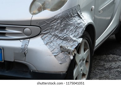 Rome, Italy - August 8, 2018: Damaged car front, repaired with duct tape