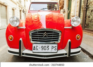 Rome, Italy - August 9, 2015: Red oltimer Citroen 2cv6 Special car stands parked on the city roadside, closeup front view with wide angle lens effect
