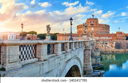 Rome, Italy. Bridge with angels and demons statue in front of Castle of the Holy Angel (Castel Sant Angelo) during evening sunset. Famous touristic landmark. Statues and street lamps medieval.