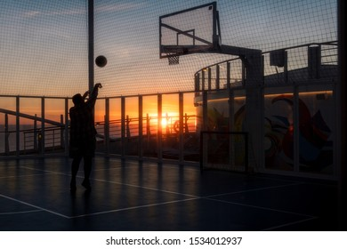 Rome, Italy - CIRCA 09/18/2018. Man playing basketball during the sunset on a cruise ship.