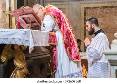 ROME, ITALY - CIRCA JANUARY 2016 - A priest saying the traditional extraordinary tridentine latin rite of the Catholic mass in the basilica of St Nicholas in Rome, with the altar servant kneeling
