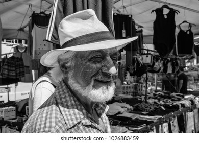 Rome, Italy - Circa September 2017: Man with a white hat walking by the shops in the flee market