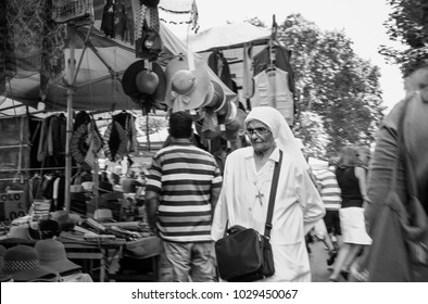 Rome, Italy - Circa September 2017: Nun walking through the flee market of Porta Portese