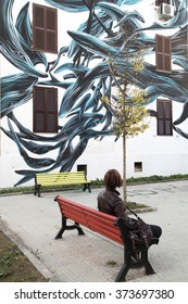 ROME, ITALY - DECEMBER 01 2015: A woman looks at a creative mural on the street of Rome in Tor Marancia suburb district AKA Shanghai. Painted by Pantonio