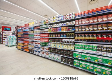 ROME, ITALY. December 05, 2018: Lanes of shelves with goods products inside a MA supermarket in Italy in Rome. Several packs of coffee on a wall of shelves. Front view, full background.