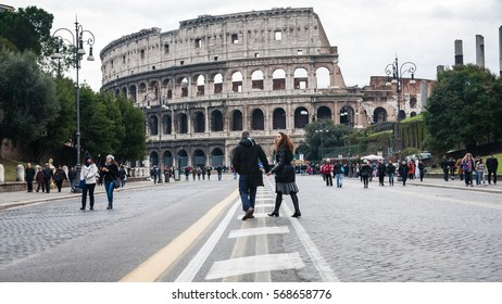 ROME, ITALY - DECEMBER 19, 2010: tourists on via dei Fori Imperiali and view of Coliseum in Rome city in winter. The Via dei Fori Imperiali was built by order of Benito Mussolini from 1924-1932