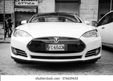 Rome, Italy - February 13, 2016 : White Tesla model S car parked on urban roadside in Rome, front view, closeup black and white photo
