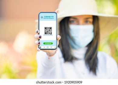 Rome, Italy, February 20, 2021. A defocused young girl, wearing a sun hat and a face mask is holding a smart phone with a digital illustration of a Covid-19 Vaccine Passport concept.