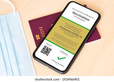 Rome, Italy, February 22, 2021. A passport and a smartphone with a Certificate of Vaccination against Covid-19 disease are arranged on a wooden table.