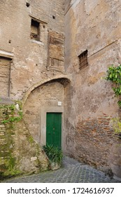 Rome, Italy - February 24, 2012: old house with a closed green door in Rome. The corner of the building is an unusual shape. Nobody seems to live there. Empty courtyard