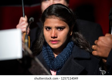 """Rome Italy, February 24, 2018: Esham Masih, daughter of Asia Bibi speech during the Ceremony outside of the Roman Colosseum, illuminated in red light and reading """"Aid to the Church that Suffers""""."""