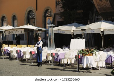 Rome, Italy - February 27, 2012: the waiter is waiting for visitors near the empty summer terrace of the restaurant near Navona's square