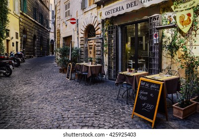 "ROME, ITALY, FEBRUARY 7, 2015: An old cobbled street in the heart of Rome with its traditional ""Osteria"" type restaurants"