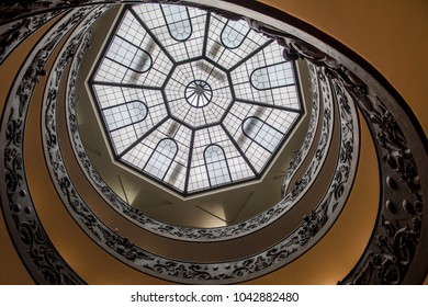 ROME, ITALY - FEBRUARY 7, 2018: Looking up the famous double spiral staircase at the exit of the Vatican Museum in Rome. The staircase was designed by Giuseppe Momo in 1932.