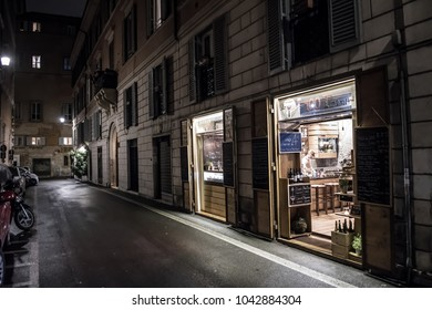 ROME, ITALY - FEBRUARY 7, 2018: Narrow alley with old-fashioned illuminated store at night in Rome